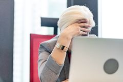 Tired mature businesswoman with head in hands at office Stock Image