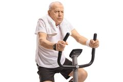 Tired mature man working out on an exercise bike Royalty Free Stock Photos