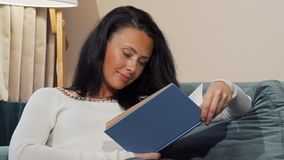 Tired mature woman falling asleep while reading at home after working day. Beautiful mid-aged female looking exhausted and sleepy. Overworking, evening leisure stock images
