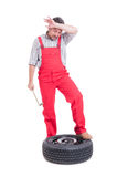 Tired mechanic after changing a new tire Royalty Free Stock Photos