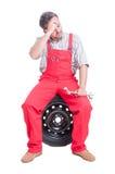 Tired mechanic sitting on car wheel and having headache Royalty Free Stock Image