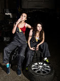 Tired mechanics sexy girls sitting on a pile of tires on a car repairs, one of the girls smoke. colorless life concept Stock Photo