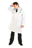 Tired medical doctor holding hand near forehead Royalty Free Stock Images