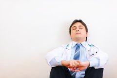 Tired medical doctor sitting on floor and relaxing Royalty Free Stock Photography