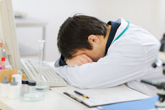 Tired medical doctor sleeping on keyboard Royalty Free Stock Photos
