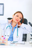 Tired medical doctor woman massaging her neck Royalty Free Stock Images
