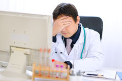 Tired medical doctor working on computer at office Royalty Free Stock Photos