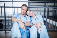 Tired medical team falling asleep on floor. At hospital Royalty Free Stock Images