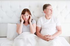 Tired middle age family couple in bed. Woman feel pain and migraine in head. Strong tension headache and stress concept. Copy space royalty free stock image