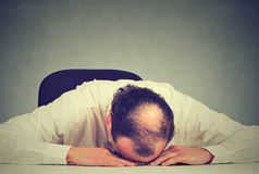Tired middle aged bald boss company employee sleeping after long working hours Royalty Free Stock Images