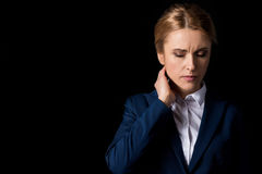 Tired middle aged business woman with headache holding hand on neck. Isolated on black Stock Image