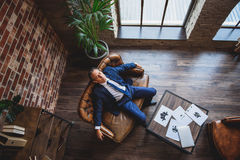 Tired middle aged businessman closing eyes. Relaxing matured man is sitting on couch. Papers are on small table. Top view Royalty Free Stock Photos