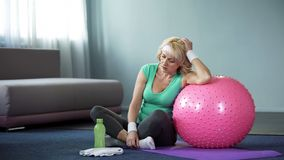 Tired middle aged female relaxing on yoga mat after active home workout, dyspnea. Stock photo stock image