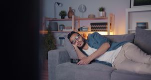 Tired middle eastern man sleeping on couch in front of tv lying alone. Tired middle eastern man is sleeping on couch in front of tv lying alone relaxing in dark stock video
