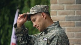 Tired military hardly breathing and taking off cap remembering war rainy weather. Stock footage stock video