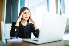 Tired minded with head pain woman thinking about way to complete task on laptop at table Royalty Free Stock Photography