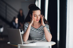 Tired minded woman thinking about way to complete a task. Beatiful female having a headache during a break in a cafe. Royalty Free Stock Photo
