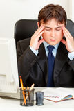 Tired modern businessman sitting at office desk Stock Photography