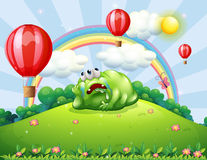 A tired monster above the hill watching the hot air balloons Royalty Free Stock Photography