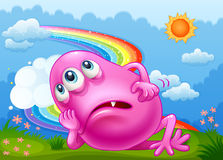 A tired monster at hilltop with rainbow in sky Stock Image