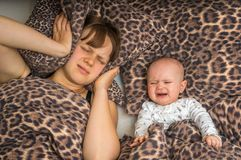 Tired mother can`t to sleep because her baby is crying. Tired mother can`t to sleep because her baby won`t stop crying Stock Photography