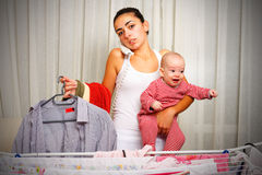 Tired mother with crying baby at home Stock Photo