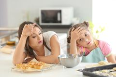 Tired mother and daughter after preparing dough Stock Photo