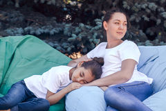 Tired mother and daughter relax on cushions in the park . Stock Photos