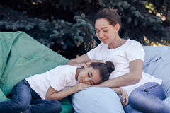 Tired mother and daughter relax on cushions in the park. Stock Photos