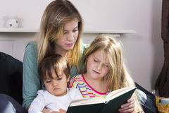 Tired mother reading book to kids Royalty Free Stock Photo