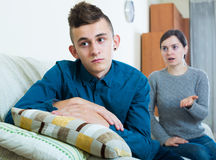 Tired mother rebuking teenage son at home. Serious mother lecturing unpleased teenager in home interior Royalty Free Stock Photos