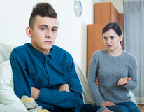 Tired mother rebuking teenage son at home. Serious mother lecturing unpleased teenager in home interior Royalty Free Stock Images