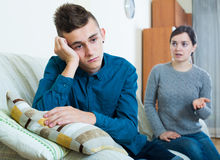 Tired mother rebuking teenage son at home. Serious mother lecturing unpleased teenager in home interior Stock Photo