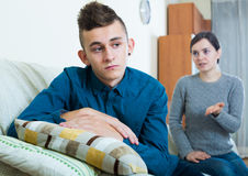 Tired mother rebuking teenage son at home. Serious mother lecturing unpleased teenager in home interior Stock Photos