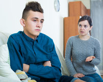 Tired mother rebuking teenage son at home. Serious mother lecturing unpleased teenager in home interior Stock Images