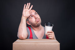 Tired mover guy holding takeaway coffee cup Stock Image