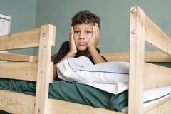 Tired multi ethnic boy lying on bed Stock Photography