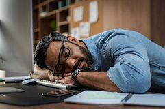 Tired businessman sleeping on computer desk stock photo