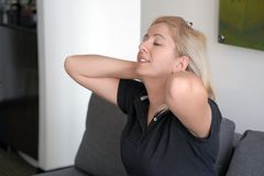 Tired neck. Woman suffering from neck pain at home on couch. A woman`s sense of fatigue, exhausted, stressed. royalty free stock images
