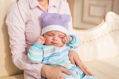Tired newborn baby boy rubbing eyes Stock Photo