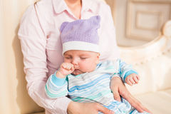 Tired newborn baby boy rubbing eyes Royalty Free Stock Photography