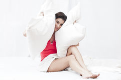 Tired of noise. Beautiful girl suffering of insomnia covering her ears with pillows because she is tired of noise royalty free stock photo