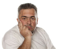 Tired obese man. Portrait of a tired and conceived obese man leaning on his hand Stock Images