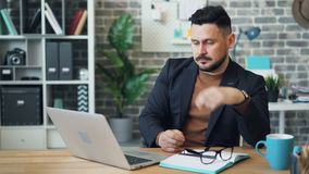 Tired office worker guy is using laptop then taking off glasses touching face