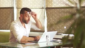 Tired office worker, hard work. The man woke up and again began to work hard for a laptop. Rubs his eyes stock footage
