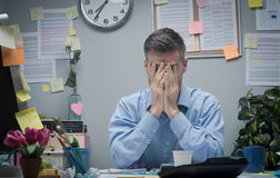 Tired office worker with head in hands Royalty Free Stock Photos