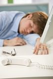 Tired office worker sleeping at desk. Tired office worker sleeping at office desk, selective focus on phone put aside Royalty Free Stock Images