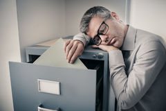 Tired office worker sleeping in the office. Tired lazy office worker leaning on a filing cabinet and sleeping, he is falling asleep standing up; stress stock images