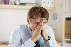 Tired office worker touching his bridge of nose to give rest to Royalty Free Stock Photography
