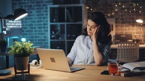 Tired office worker using computer and yawning working late at night alone stock footage